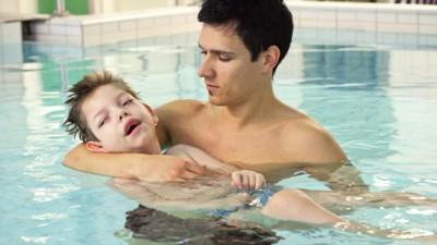 kinderintensivpflege kind mit pfleger im Wasser