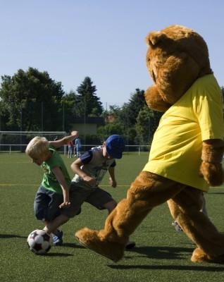 Maskottchen Paulchen spielt Fußball mit Kindern